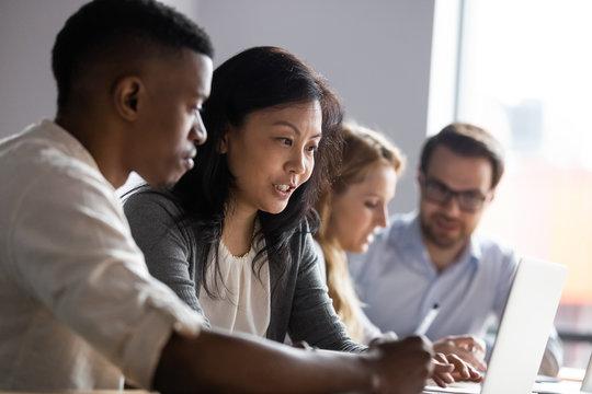 Asian businesswoman mentor teaching African American intern, using laptop