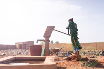 Joyful Native African Young Woman Carrying Healthy Water in a village