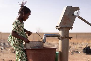 Joyful West African Girl Saving Healthy Water in a rural village