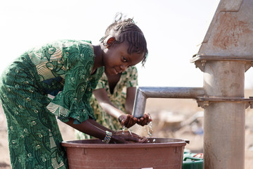 Poor West Africa Youngster with pure Water in a rural village