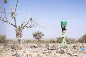 Tiny African ethnicity Women Working with fresh Water as a drought symbol
