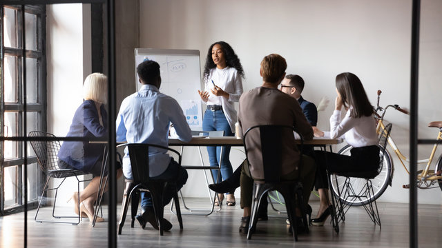 Diverse workers listening african businesswoman tell about strategy at meeting