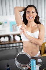 Cheerful young woman applying antiperspirant on armpit