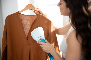 Young lady using clothes steamer to freshen up shirt