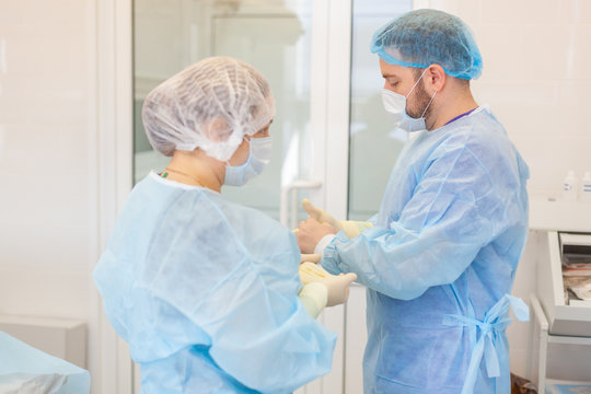 Hospital. Surgeon operates in the operating room. Profile view of a medical assistant helping a surgeon put on his gloves and medical gown in an operating room