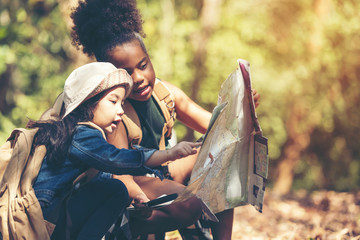 Obraz Group family children checking map for explore and find directions in the camping jungle nature and adventure. Tourism kids travel for destination and leisure trips for education relax nature park.  - fototapety do salonu