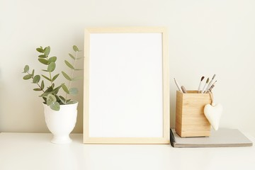 Minimalist interior empty frame mock up on white background, eucalyptus and wooden decoration.