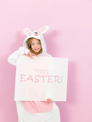 pretty blonde girl with cozy rabbit costume and white sign with happy easter written on it is posing in the studio