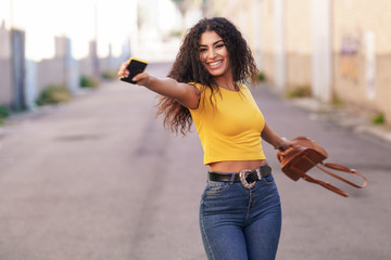 Happy Arab woman with open arms in the street.
