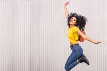 Happy Arab woman jumping in urban background.