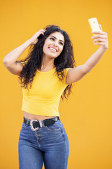 Young Arab woman taking selfie photograph with smartphone.
