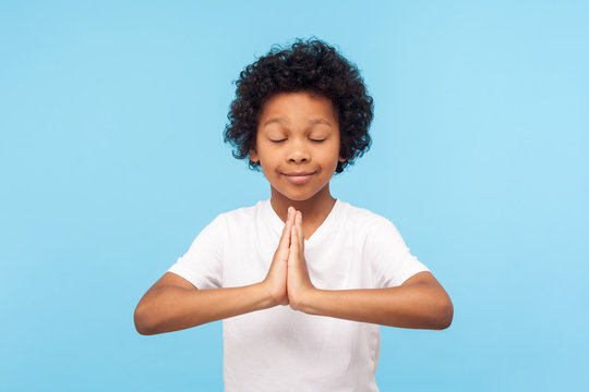 Portrait of nice little curly boy holding arms in prayer and meditating with closed eyes, smiling feeling calm relaxed with peaceful mind, yoga practice. indoor studio shot isolated on blue background