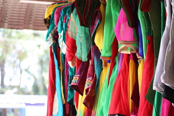 close up of green cloth, red cloth, purple cloth,blue cloths, rose cloths hanging on rod in the street cloths market in chennai,