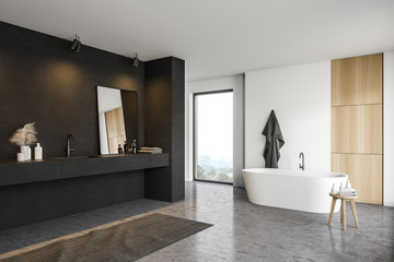 Black and white bathroom corner with tub and sink