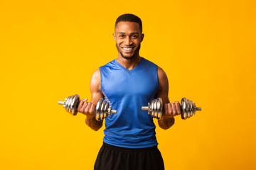 African bodybuilder pumping up dumbbells at studio