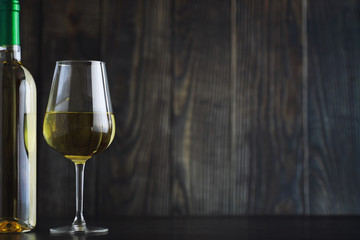 Transparent bottle of white dry wine on the table. White wine glass on a wooden background.