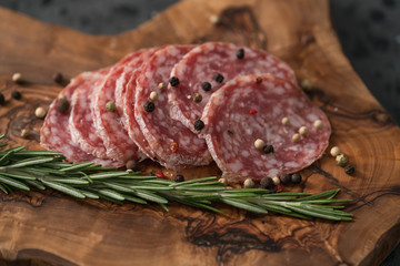 Sliced salame milano sausage on olive wood board with rosemary and pepper