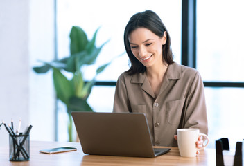 Portrait of smiling woman working on laptop with tea