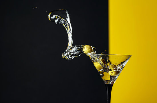 Martini with green olives splash.