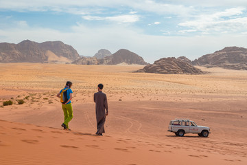 Young girl with bedouin local guide on an offroad tour on a vast Wadi Rum red sand desert, Middle East, Jordan