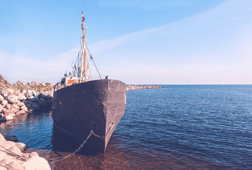 In de dag Schip old metal ship is moored to the rocky shore of lake Ladoga