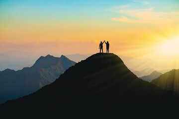 The silhouette of lovers on the top of the mountain During sunset time