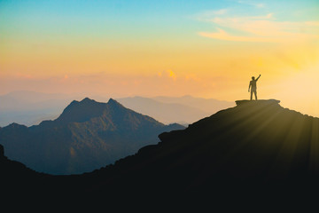 The silhouette of a man with a cheerful raise in his hand on the top of the mountain During sunset time The concept of effort and success Fotomurales
