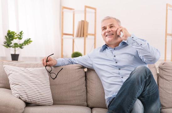 Senior man talking on mobile phone at home