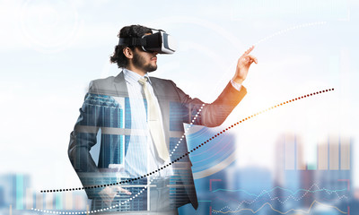 Handsome elegant businessman experiencing impressive virtual reality and business city at backdrop