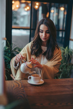 Woman pouring tea into the cup in cafe