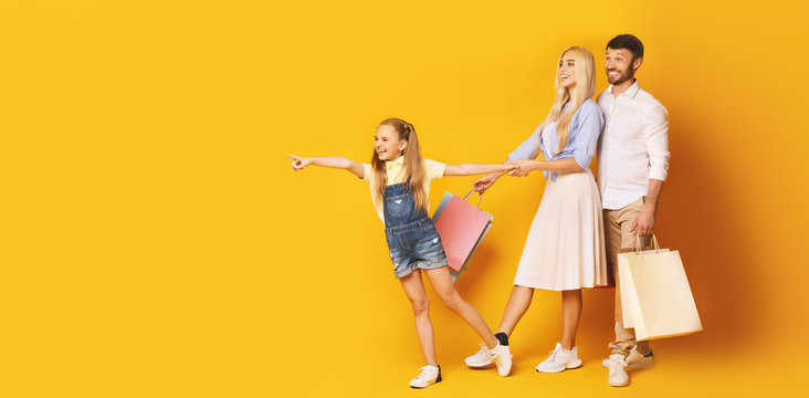 Little Daughter Pointing Finger Aside Shopping With Parents, Yellow Background