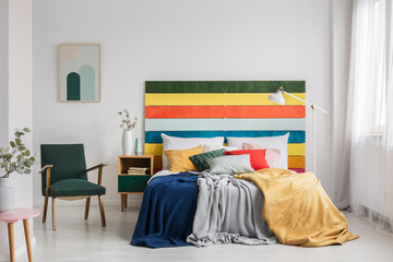 Retro armchair in modern bedroom interior with rainbow colored headboard