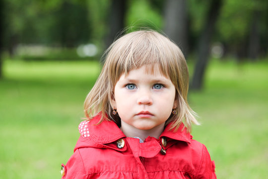 Serious or sad baby girl in red. Caucasian blonde real people girl close portrait outdoor.