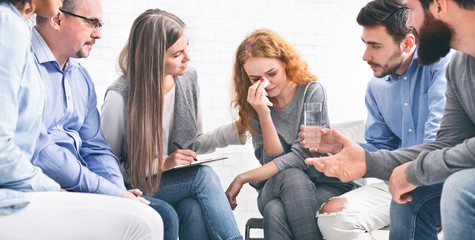 Depressed crying woman receiving empathy from Support Group members