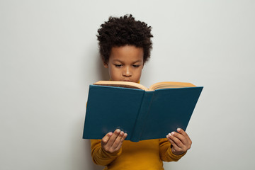 Serious black kid boy reading a book on white background