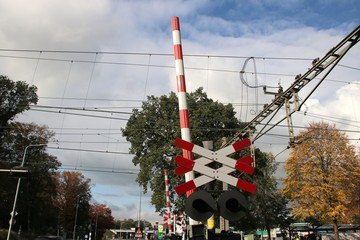 Red and white barrier and cross at railroad crossing in town 't Harde in the Netherlands