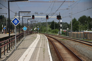 Red signs above railroad tracks heading to Rotterdam at Gouda Railway Station