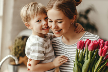 happy mother's day! child son gives flowers for  mother on holiday .