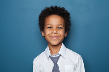 Portrait of black kid boy pupil on blue background. Happy child student school boy