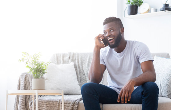 Cheerful african guy making a date with girlfriend by phone