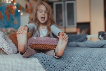 Cheerful happy little girl is playing on the sofa in the room Fototapete