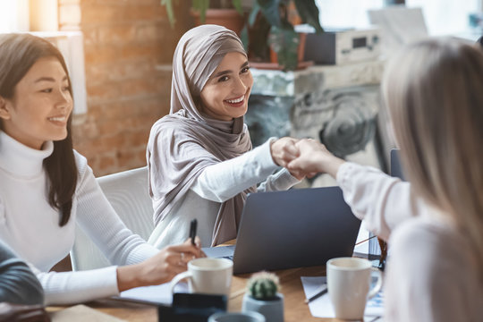 Two girls business colleagues shaking hands in office