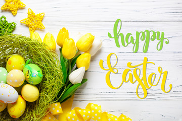 Happy Easter. Congratulatory easter background. Easter eggs and flowers. Selective focus. Top view.