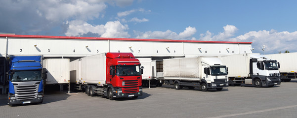 LKW´s beim beladen am Warenlager einer Spedition/ Transportunternehmen /// Trucks loaded at the warehouse of a forwarding agent/transport company