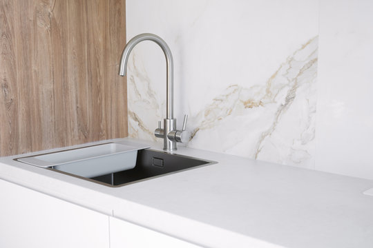 Kitchen sink and faucet on white kitchen