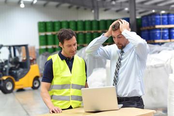 Arbeiter und Vorgesetzter in einem Warenlager // Manager and Workers in logistics company