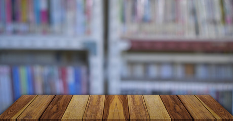 Empty wooden table over blurred bookshelf background. education concept.