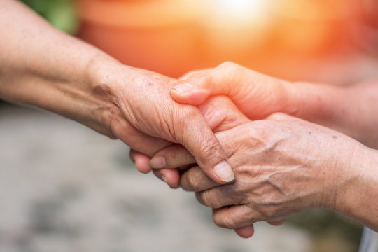 Aging society concept. Hands of old people holding support each other in nursing home