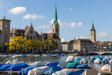 Waterfront of Limmat river in Zurich, Switzerland with ships, churchs and other buildings