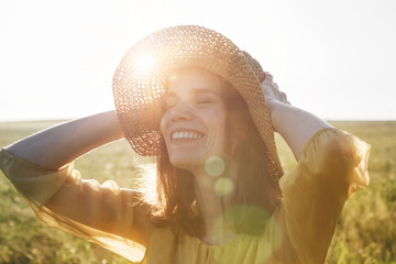 Portrait of happy pretty woman with hat smiling and enjoying summer sunlght in meadow